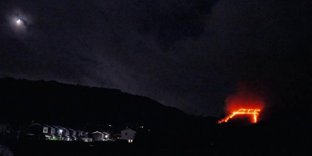 鳥居形送り火と三日月の写真